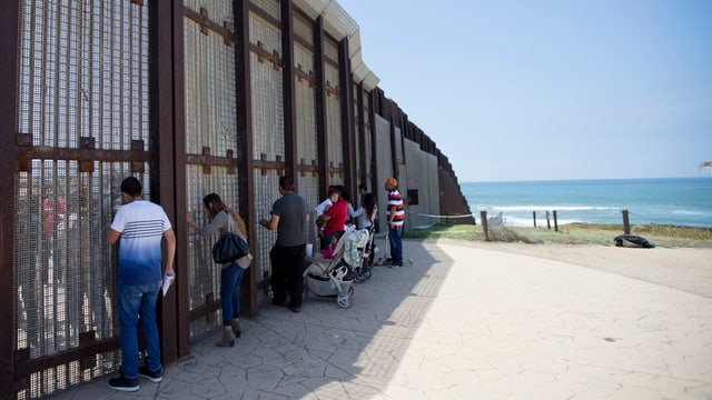 Menschen stehen am Grenzzaun, im Hintergrund das Meer.