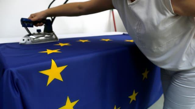 Eine Näherin streicht mit einem Bügeleisen über eine EU-Flagge.