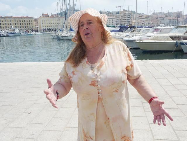 Eine ältere Frau steht einem Hafen, sie hat ihre Arme ausgestreckt und singt.