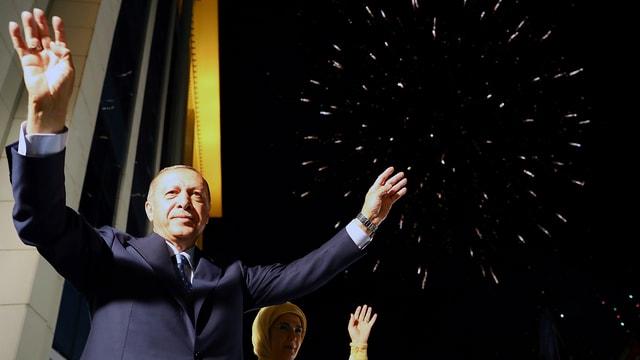 Purtret dad Erdogan che tegna ils mauns en l'aria.
