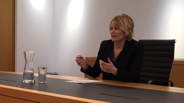 Eine Frau sitzt in einem Sitzungszimmer und referiert.