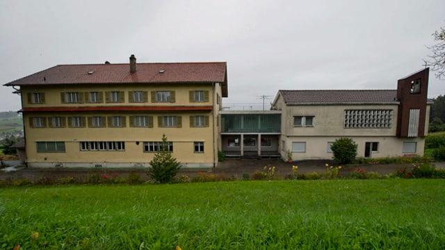 Zwei Gebäude auf einer grünen Wiese