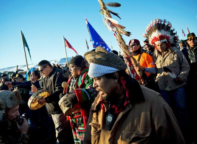 Indianer mit Fahnen und Trommeln.