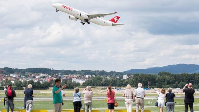 Menschen an der Landebahn beobachten ein Swiss-Flugzeug beim Abheben.
