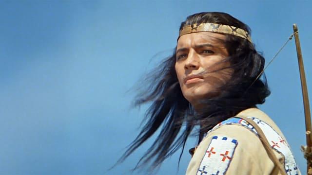 Mann in indianischer Kleidung, schaut verträumt in die Ferne.