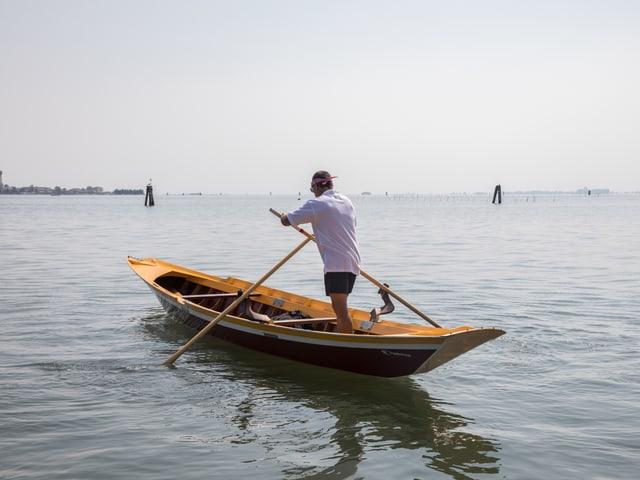 Ruderer steht alleine in einem Boot.