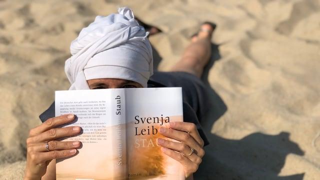 Annette König liegt im Wüstenstaub. Hat ein Beduinentuch um den Kopf und liest im Buch «Staub».