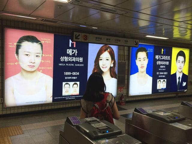 Werbung mit Vorher-Nachher-Bildern an einer U-Bahn-Station in Seoul.