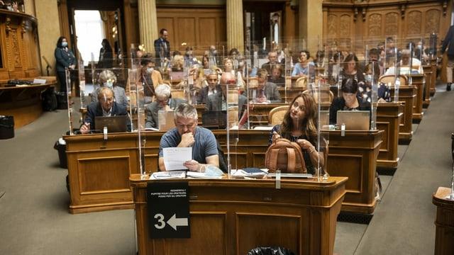 Blick in den Nationalratssaal, wo die Parlamentarier einzeln hinter Plexiglasscheiben sitzen.