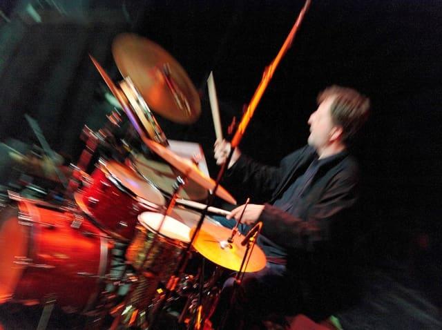 Ein Mann hinter einem Schlagzeug in buntem Licht.