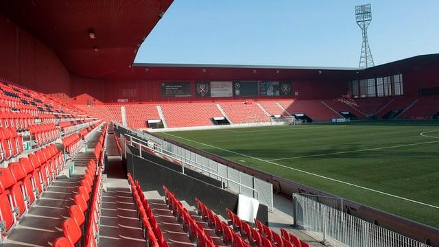 Zu sehen ist ein Teil der rotbestuhlter Tribüne und ein grüner Kunstrasen eines Fussballstadions.