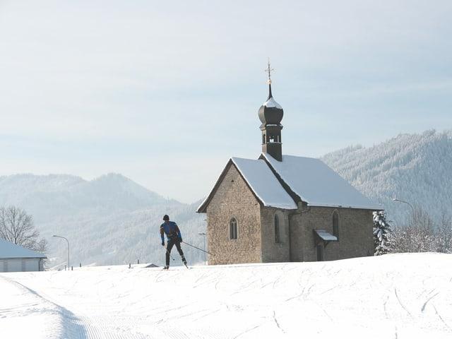 Langläufer vor Kapelle.