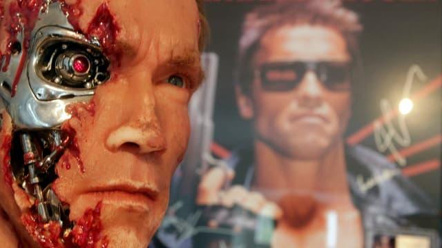 Unter der Maske eines Menschen verbirgt sich der metallische Kopf eines Roboters.