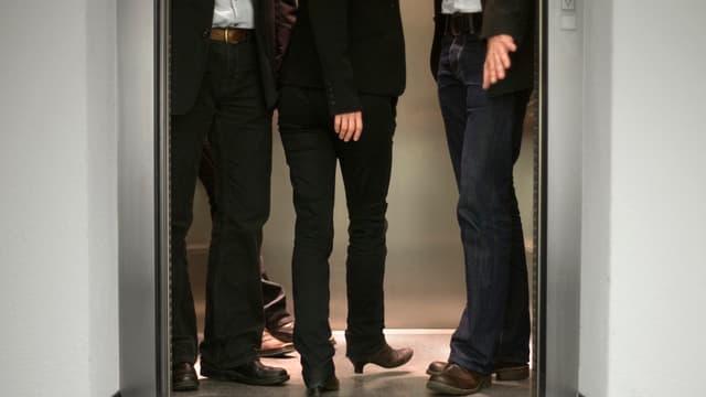 Zwei Männer und eine Frau (Hüfte abwärts zu sehen) betreten einen Lift.