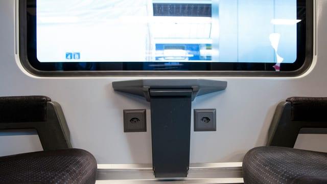 Zwei graue Sitze in einem Bahnwagen, dahinter das Fenster. Unter dem Fenster zwei graue Steckdosen.