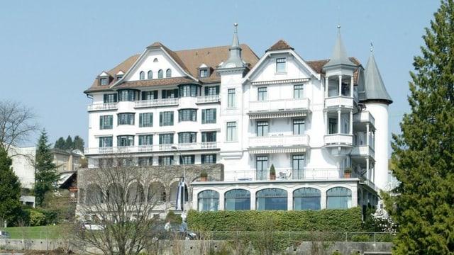 Ein Hotelgebäude an einem See - im Vordergrund ein Motorboot.