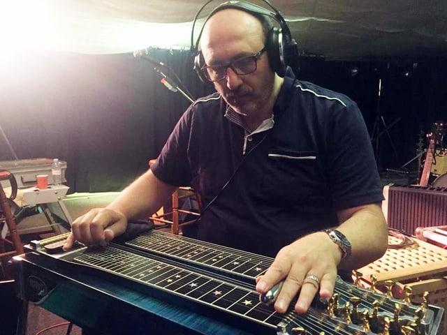 Mann spielt liegendes Saiteninstrument.