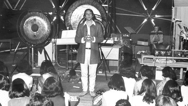 Stockhausen vor grossen Gongs auf einer Bühne vor jungem Publikum