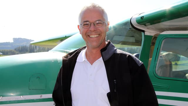 Pascal Miller mit Brille, weissem Hemd und dunkler Weste steht vor einem grünen Sportflugzeug.