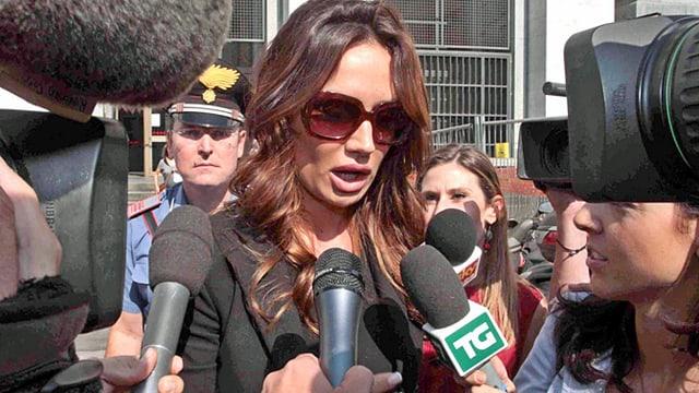 Frau wird von Journalisten belagert.