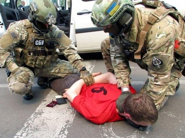 Zwei Sicherheitskräfte halten einen Mann am Boden fest