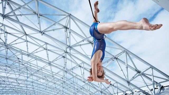 Tänzerin hängt an einem Seil an der Dachkonstruktion der Halle..