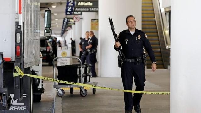 Ein Polizist mit Gewehr in einer grossen Halle