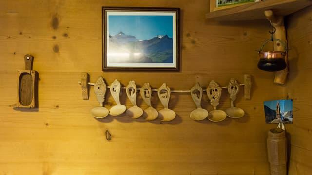 Ein Holzwand mit verschiedenen Utensilien für die Käseproduktion.