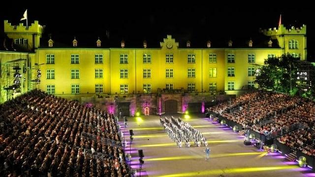 Eine Militärmusikformation marschiert vor der Tribüne und der Kulisse des Gelb beleuchteten Kasernengebäudes.