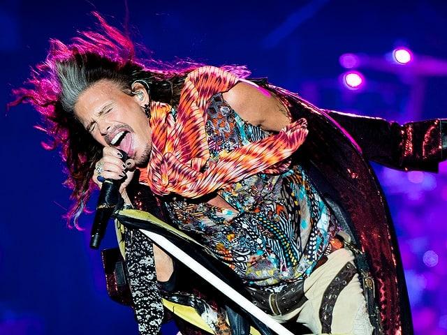 Steven Tyler mit farbigen Kleidern am singen.