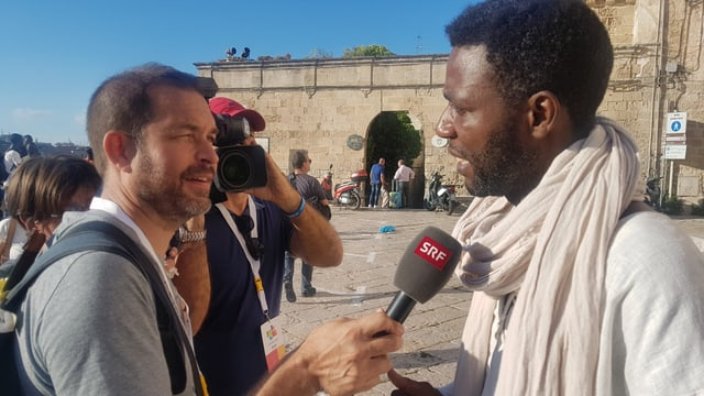 Ein Mann mit heller Hautfarbe streckt einem anderen Mann mit dünklerer Hautfarbe ein Mikrophon entgegen. Hinter ihnen ist eine Kamera zu erkennen, die auf den Interviewten gerichtet ist.