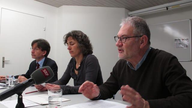 Die drei Verantwortlichen sitzen am Tisch und sprechen zu den Medien