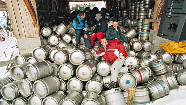 Drei Männer sitzen auf zig Bierfässern