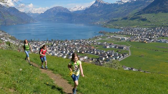 Eine Frau und zwei Mädchen Wandern auf einem Weg mit Blick auf einen See.
