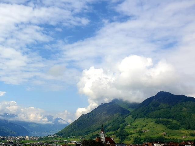 Quellwolken an einem Berg, darüber eine flockige Wolkenschicht.
