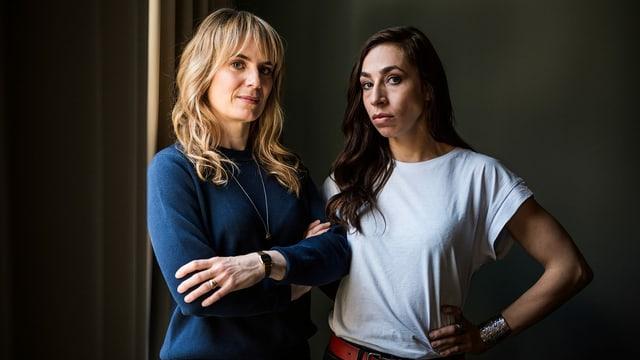 Zwei Frauen stehen nebeneinander und schauen ernst in die Kamera