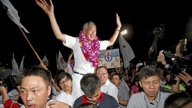 Lee Hsien Loong wird von Anhängern getragen.