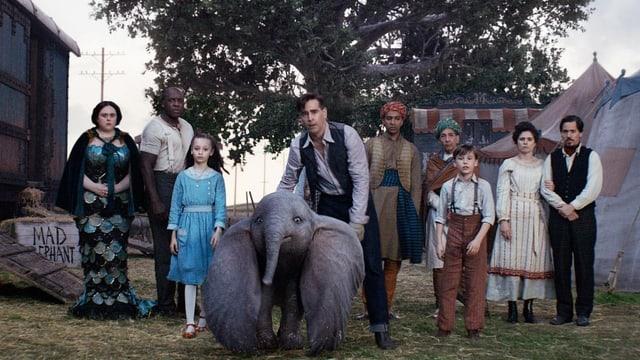Neun Menschen stehen um einen kleinen Elefanten herum.