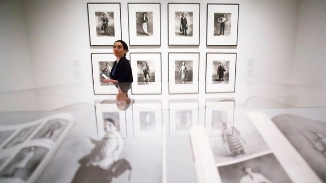 Eine Frau läuft durch ein Fotomuseum. Auf der Wand hängen schwarz-weiss-Bilder.