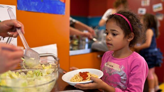 Ein Mädchen hält einen Teller Spaghetti.