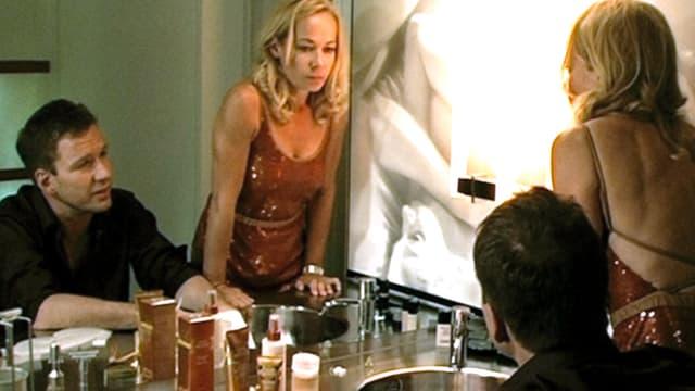 Ein Mann und eine Frau im Badezimmer vor dem Spiegel.