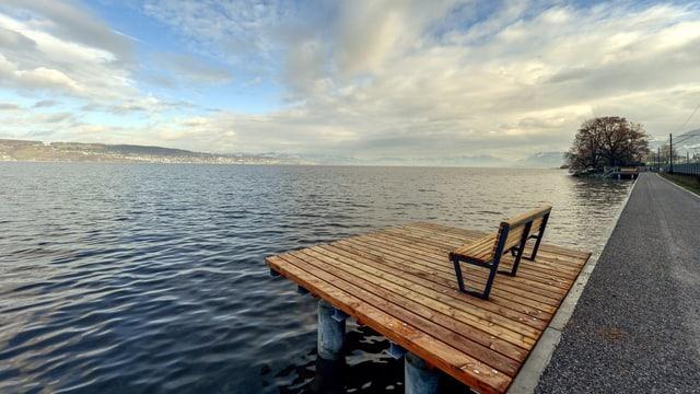 In den Zürichsee ragt eine Plattform mit einer Sitzbank darauf.