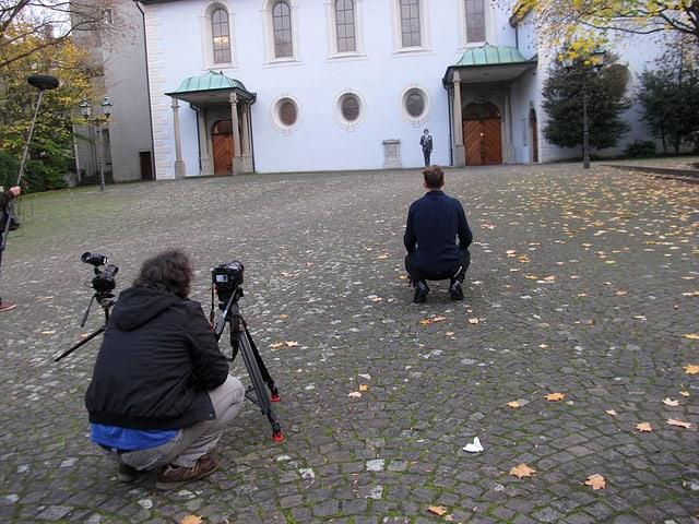 Im Hintergrund steht vor einer Kirche ein Mann, davor knien zwei Männer vor ihren Kameras die den Mann vor der Kirche filmen.