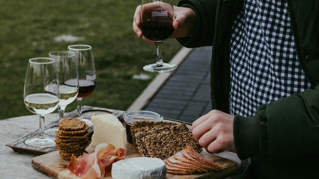Käseplatte und Weingläser gefüllt mit Rot- und Weisswein. Ein Mann hält ein Glas Rotwein in der Hand.