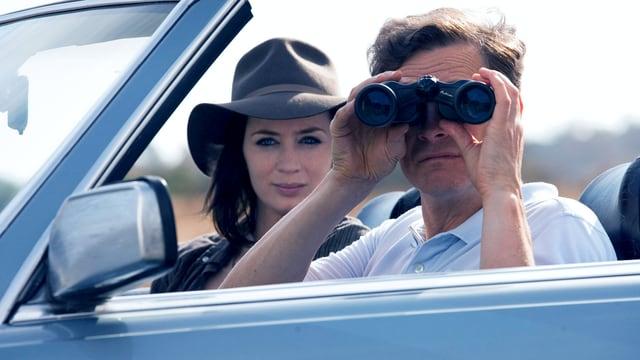 Eine Frau und ein Mann sitzen in einem Cabriolet. Die Frau trägt ein Hut und der Mann blickt durch einen Feldstecher.