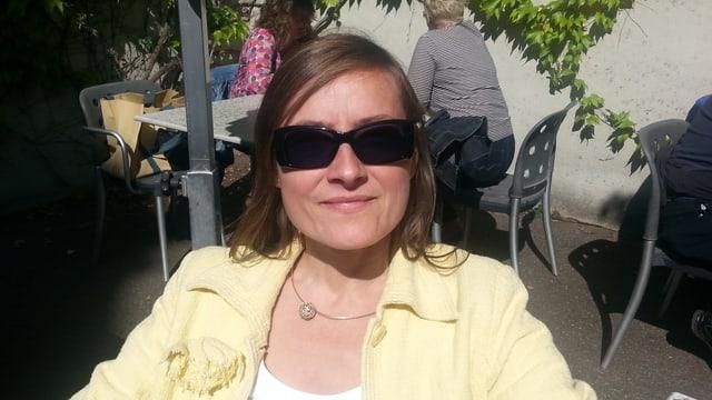 Frau Sibylle Oser sitzt in einem Gartenrestaurant