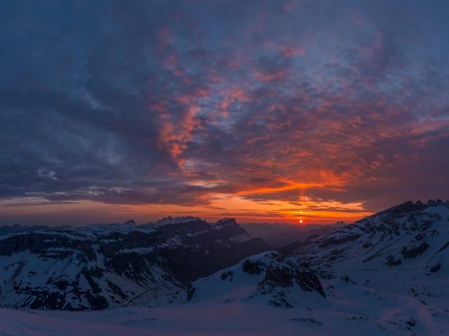 Sonnenaufgang in den Schneebergen mit Wolken am Himmel und orangem und gelbem Horizont.