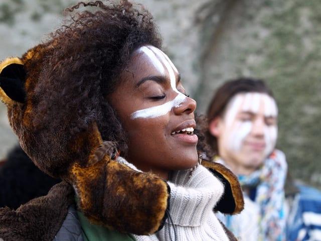 Frau mit weissen Linien im Gesicht und geschlossenen Augen