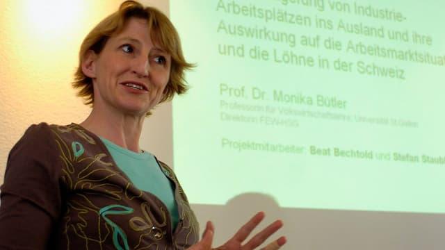 Monika Bütler referiert vor Projektionswand.