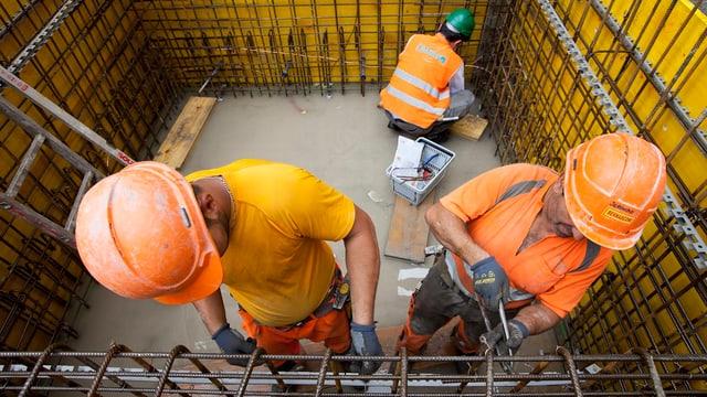 Bauarbeiter (Eisenleger) verbinden Armierungseisen in einer Schalung.